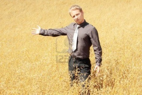 5400905-young-modern-farmer-in-suit-standing-in-field-of-oats